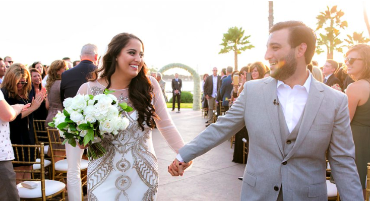 Wedding Photos with Couple Holding Hands Walking Down Aisle. Bridal Hair and makeup by Vanity Belle in Orange County (Costa Mesa) and San Diego (La Jolla)