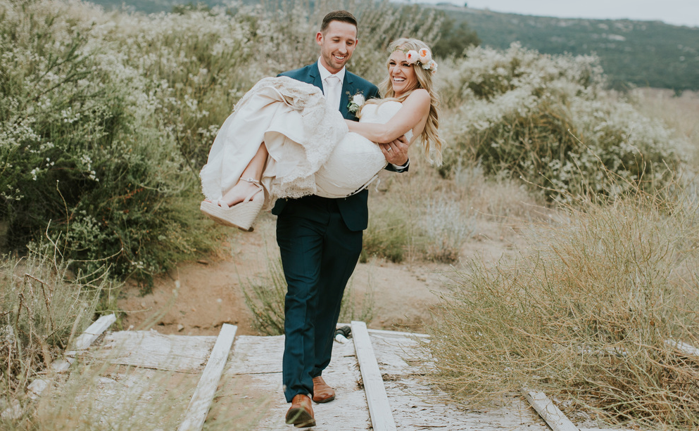 Wedding Photos Outdoors with Husband Carrying Bride. Bridal Hair and Makeup by Vanity Belle in Orange County (Costa Mesa) and San Diego (La Jolla)