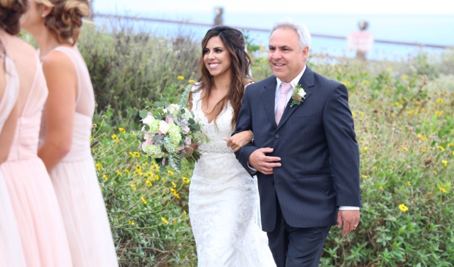 Brunette Bride Walking Down Aisle outside holding Bouquet in Wedding Photos. Bridal hair and makeup by Vanity Belle in Orange County (Costa Mesa) and San Diego (La Jolla)