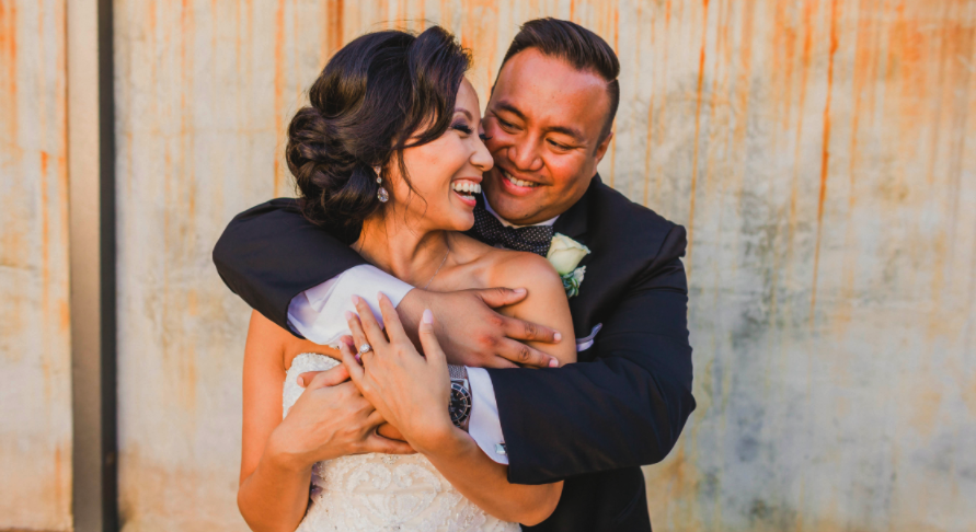 Asian Bride with Updo hugging husband smiling in Wedding Photos Outside. Bridal Hair and Makeup by Vanity Belle in Orange County (Costa Mesa) and San Diego (La Jolla)