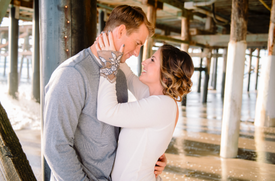 Engagement Photos Under Pier at Beach with Couple Looking into Eyes. Hair and Makeup done by Vanity Belle in Orange County (Costa Mesa) and San Diego (La Jolla).
