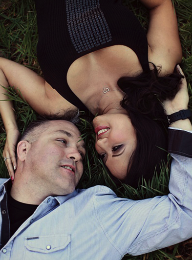 Engagement photo shoot with couple laying downin nature looking into each others eyes. Hair and Makeup done by Vanity Belle in Orange County (Costa Mesa) and San Diego (La Jolla).