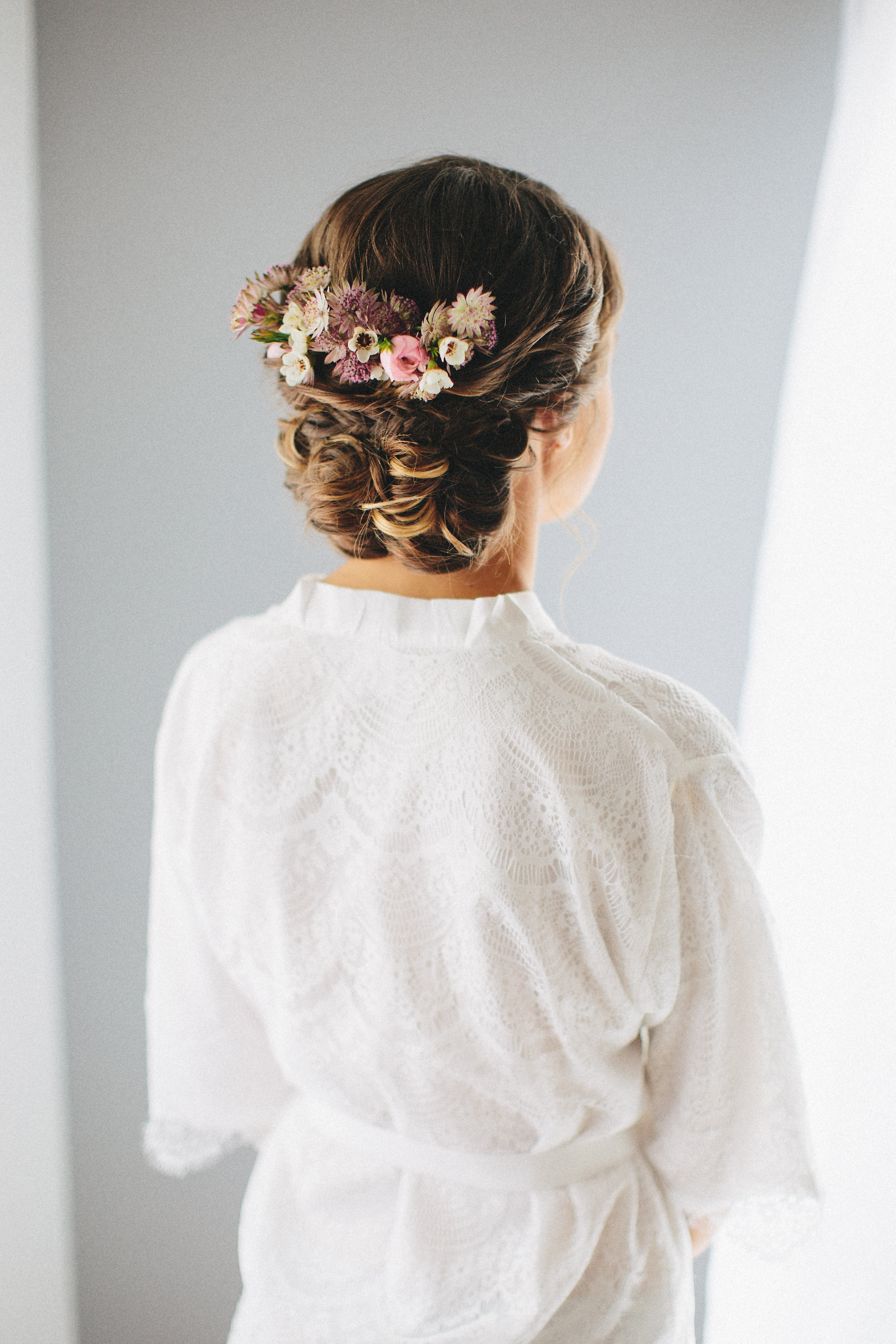Wedding Updo from Behind with Flowers and Bride Wearing Robe. Bridal hair and makeup by Vanity Belle in Orange County (Costa Mesa) and San Diego (La Jolla)