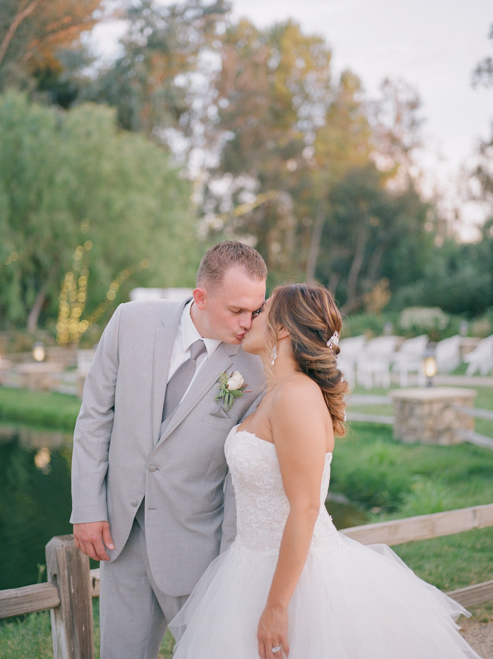 Wedding Hairstyle Down Medium Length with Bride Kissing Husband Outdoors in Photos. Wedding Hair and Makeup by Vanity Belle