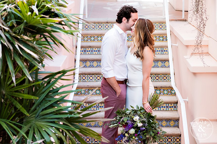 Wedding Photos with Brunette Bride wearing Headband holding Bouquet kissing husband. Bridal Hair and Makeup by Vanity Belle in Orange County (Costa Mesa) and San Diego (La Jolla)