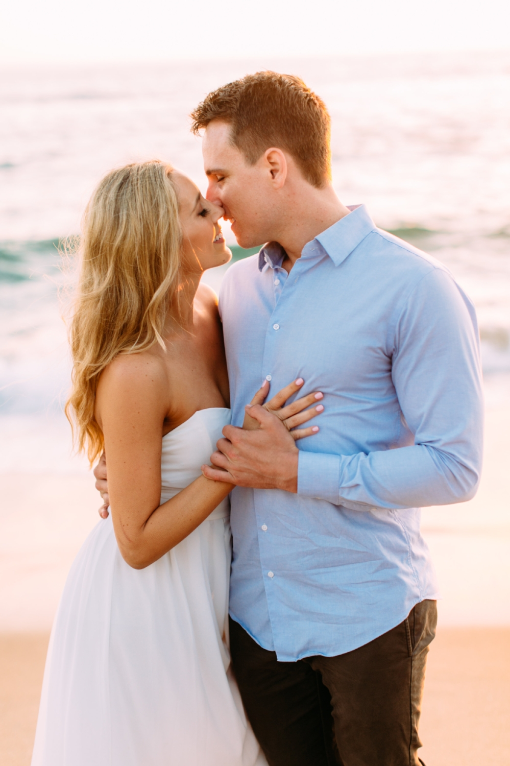 Engagement Photos Kissing Poses at Beach. Hair and Makeup done by Vanity Belle in Orange County (Costa Mesa) and San Diego (La Jolla).