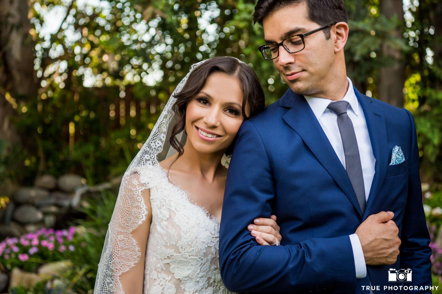 Petite Hispanic Bride in Lace Veil Posing inWedding Photos with Husband. Bridal Hair and Makeup by Vanity Belle in Orange County (Costa Mesa) and San Diego (La Jolla)