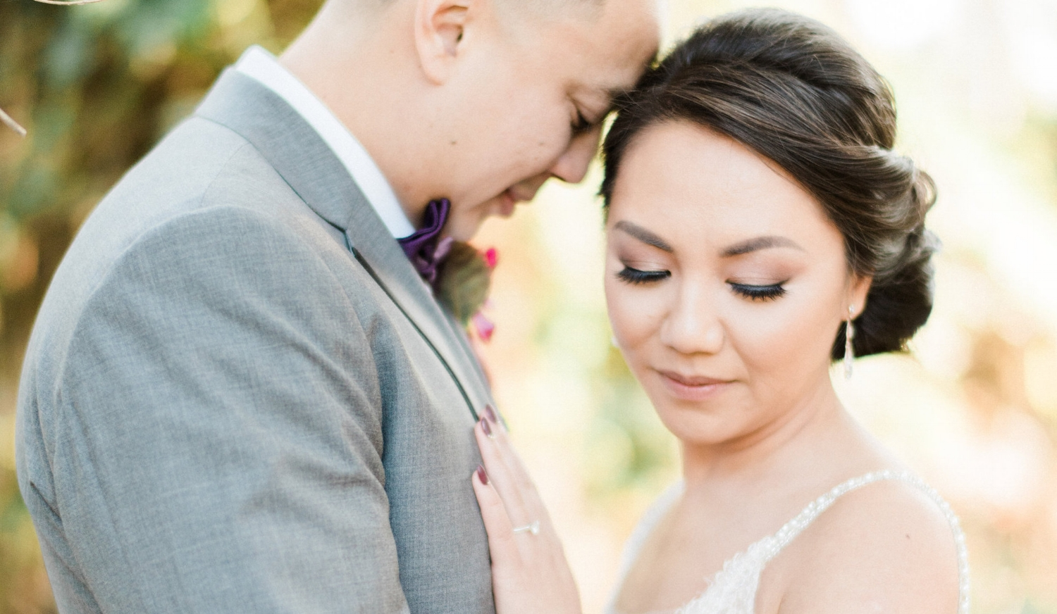 Asian Bride with Simple Makeup and Updo Hairstyle with Husband outside in Wedding Photos. Bridal Hair and Makeup by Vanity Belle in Orange County (Costa Mesa) and San Diego (La Jolla)