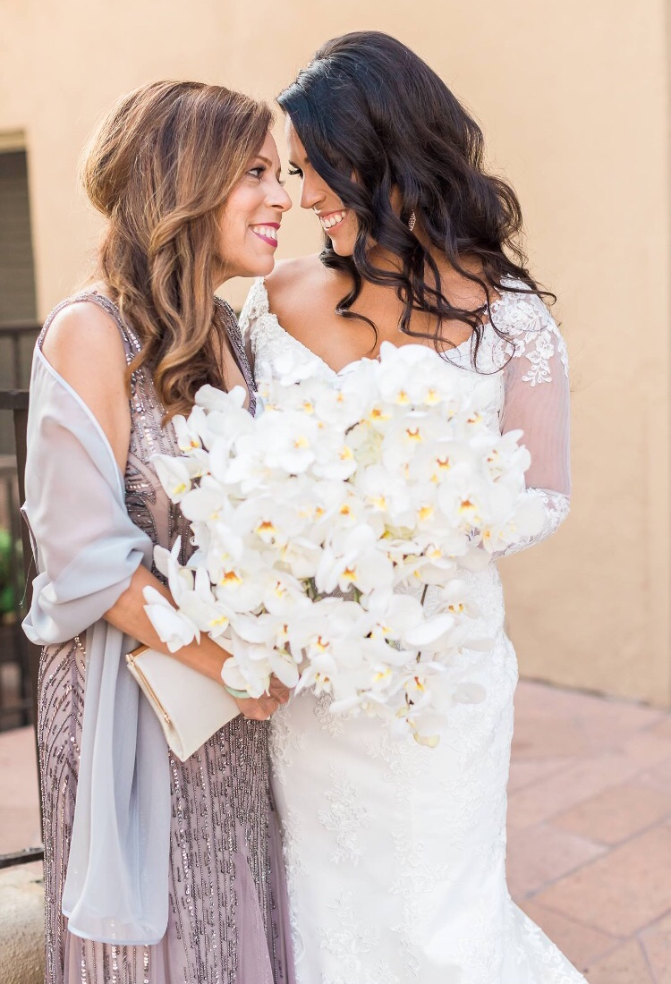 Brunette bride and maid of honor in wedding day photos with beachy curled hair and orchid bouquet Surf & Sand in Laguna Beach, CA. Bridal hair and makeup by Vanity Belle in Orange County (Costa Mesa) and San Diego (La Jolla). thevanitybelle.com