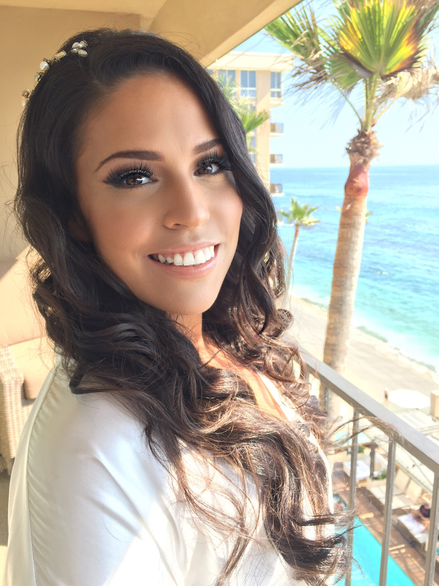 Brunette bridal makeup with sparkly smokey eye and curled hair down at Surf & Sand beach wedding in Laguna Beach. Wedding day Hair and Makeup by Vanity Belle in Orange County (Costa Mesa) and San Diego (La Jolla)