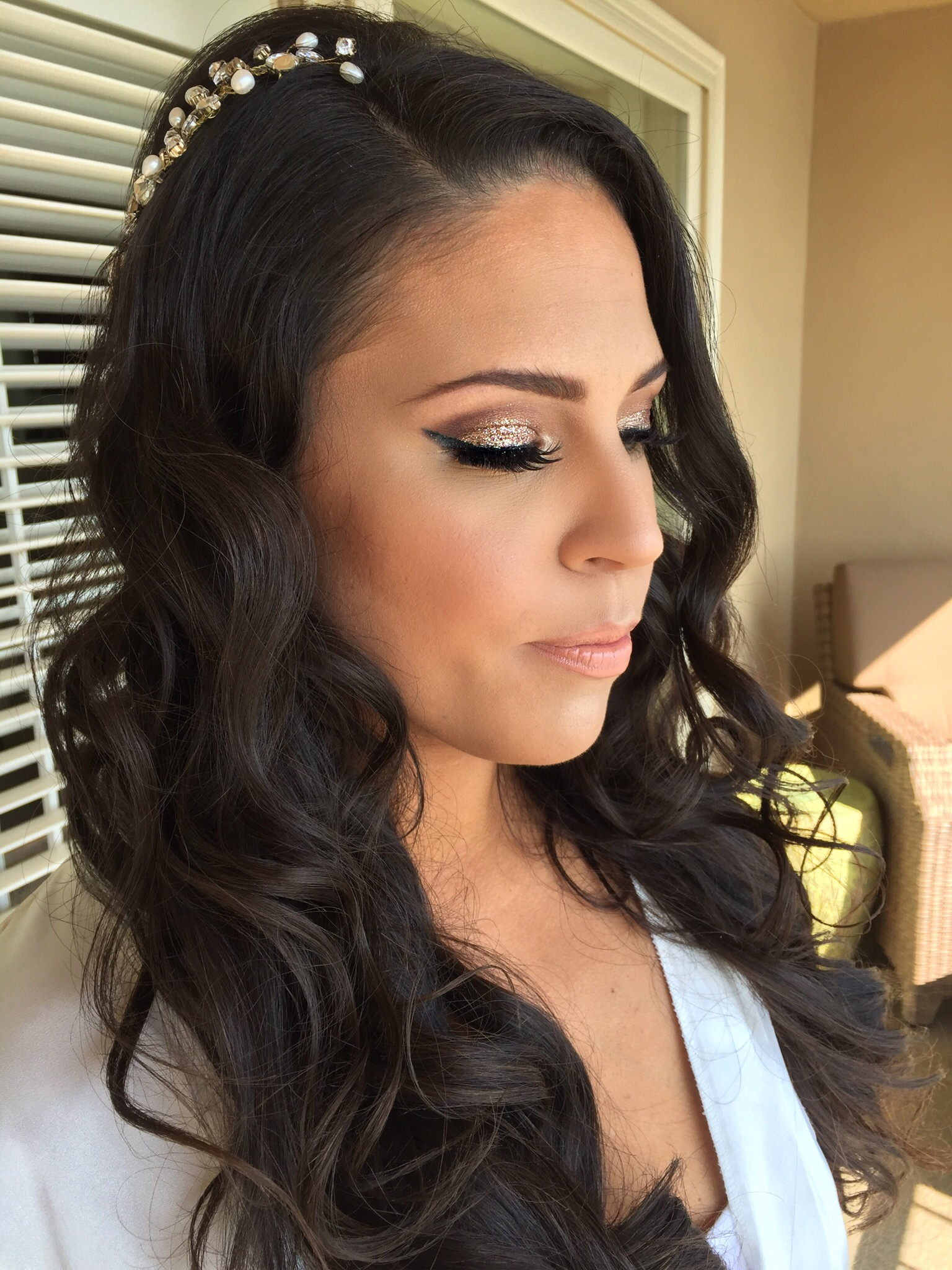 Brunette bridal makeup with sparkly smokey eye and curled hair down with accessory at Surf & Sand beach wedding in Laguna Beach. Wedding day Hair and Makeup by Vanity Belle in Orange County (Costa Mesa) and San Diego (La Jolla)
