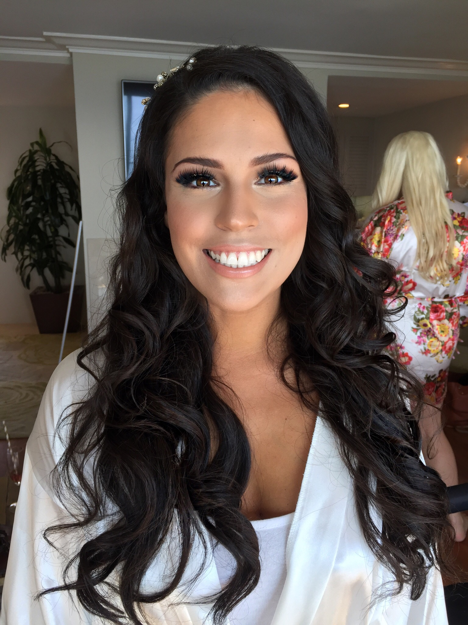 Brunette bridal makeup with sparkly smokey eye and long curled hair down with accessory at Surf & Sand beach wedding in Laguna Beach. Wedding day Hair and Makeup by Vanity Belle in Orange County (Costa Mesa) and San Diego (La Jolla)