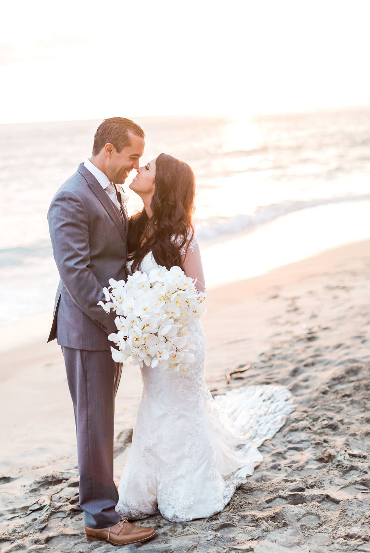 Beach wedding photography with husband and wife with white orchid bouquet at Surf & Sand Resort in Laguna Beach, CA. Bridal hair and makeup by Vanity Belle in Orange County (Costa Mesa) and San Diego (La Jolla). thevanitybelle.com
