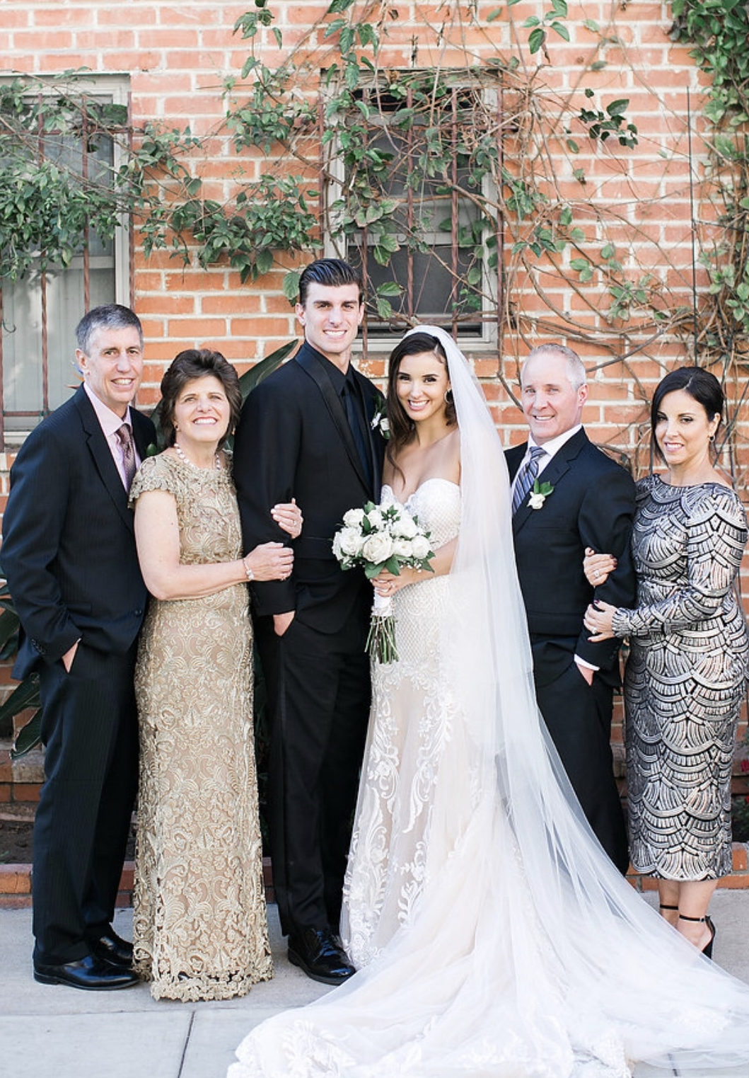 Brunette Bride with groom and family for wedding day photo. Bridal look by Vanity Belle Orange County (Costa Mesa) and San Diego (La Jolla). thevanitybelle.com