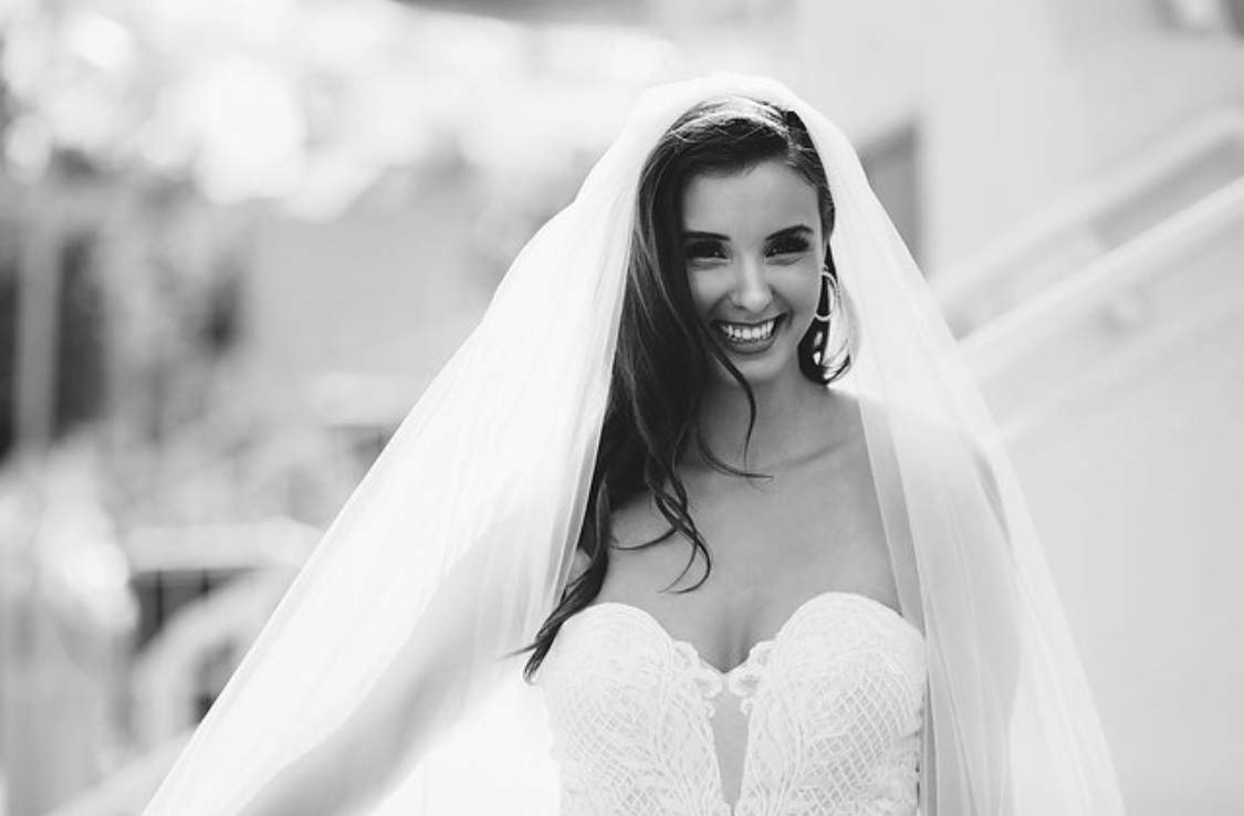 Classic black and white bridal beauty. Brunette bride in wedding day photo with long wavy curls under her veil. Hair and makeup by Vanity Belle Orange County (Costa Mesa) and San Diego (La Jolla). thevanitybelle.com