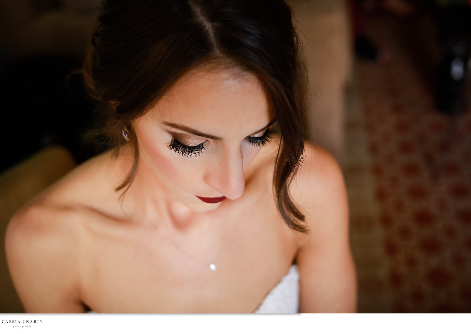 Brunette bride with side up-do, bold lip and smokey eye makeup. Bridal Beauty by Vanity Belle in Orange County (Costa Mesa) and San Diego (La Jolla). thevanitybelle.com