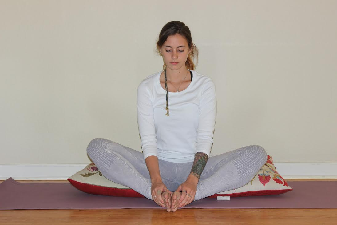 BUTTERFLY VARIATION . You can also place pillows underneath your knees and stay sitting upright if you feel any discomfort in your hips.    *If you have sciatica, elevate the hips by sitting on a pillow. If you have any lower back disorders that are aggravated by forward bending, do not allow the spine to round: keep the back as straight as possible or do the reclining version by keeping your legs where they are and lying on your back.    Coming out: slowly roll up, lean back on your hands and straighten each leg.