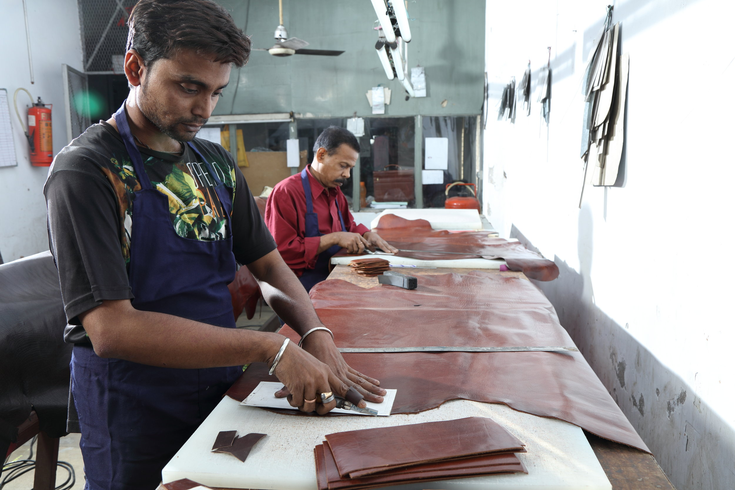 hand cutting - Once the orders are placed the merchandiser orders the leather and materials. The leather/ materials come into the stores, are measured and checked. The leather is sent for hand cutting or clicking (cutting by machines). The cut parts are counted, inspected and sent for splitting ( the  parts are split and made thinner to a pre -determined gauge for easier stitching). Materials are likewise checked, measured, cut and made ready for production.