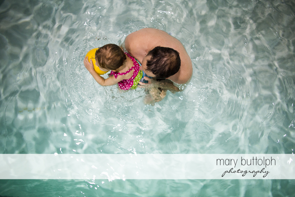Overhead shot of girl and her father playing in the pool at Skaneateles