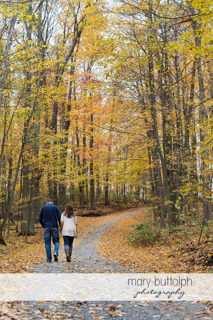 Couple stroll in the woods at Skaneateles Engagement