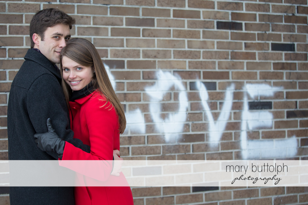 """Couple stand in front of a brick wall with the word """"Love"""" at Skaneateles Engagement"""