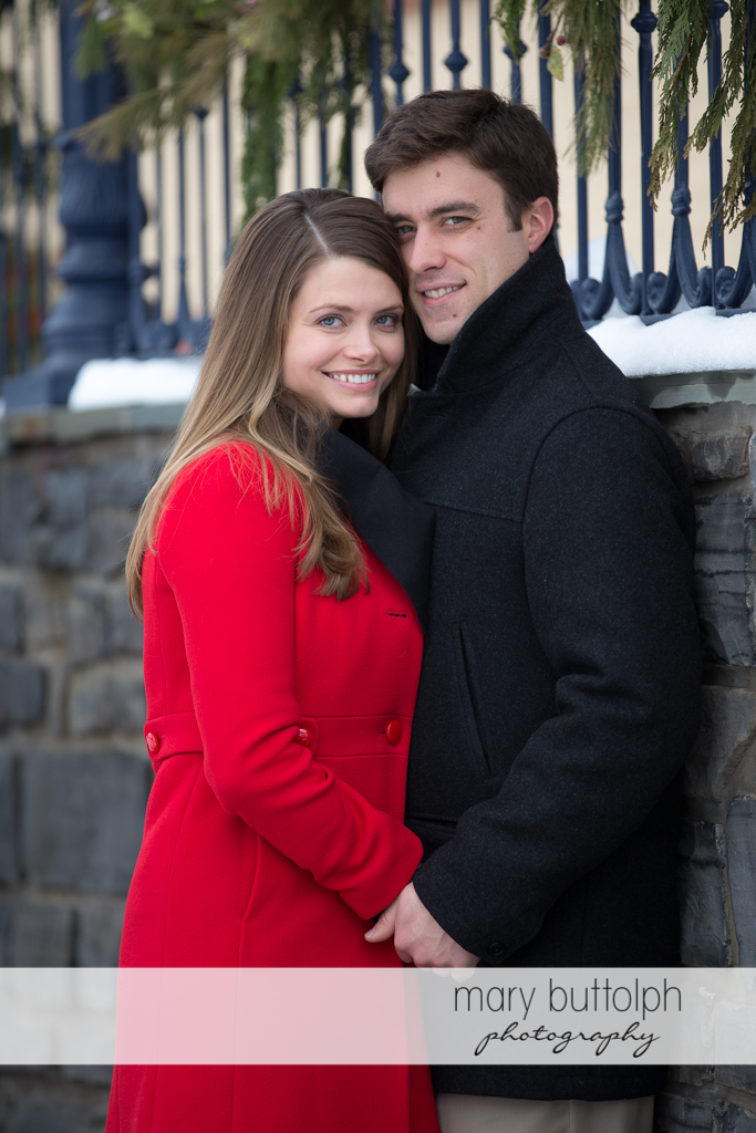 Couple pose in front of a fence wall at Skaneateles Engagement