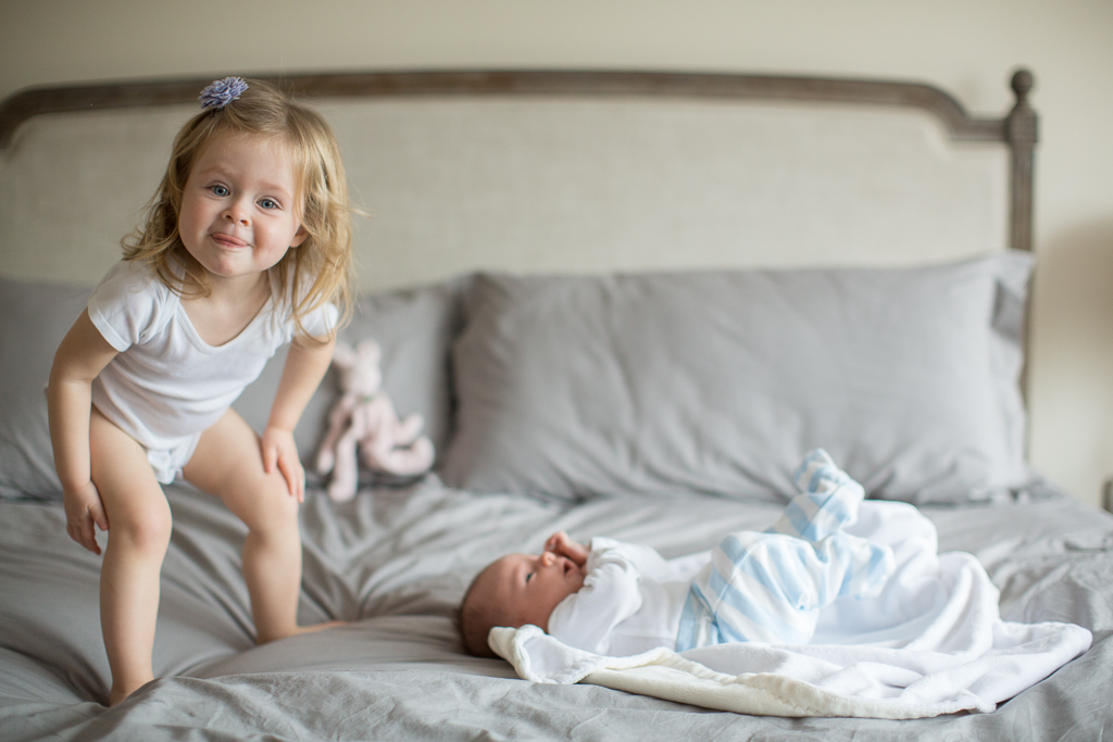 Big sister looks after her new baby brother at Skaneateles Newborn Photography