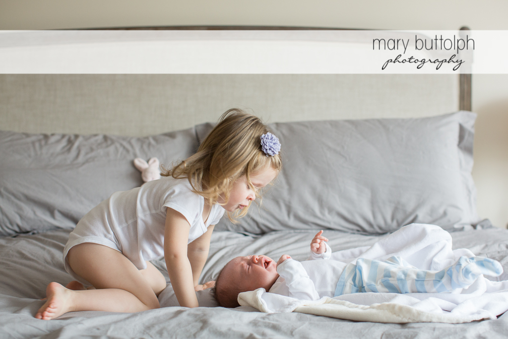 Girl comforts her crying baby brother in bed at Skaneateles Newborn Photography