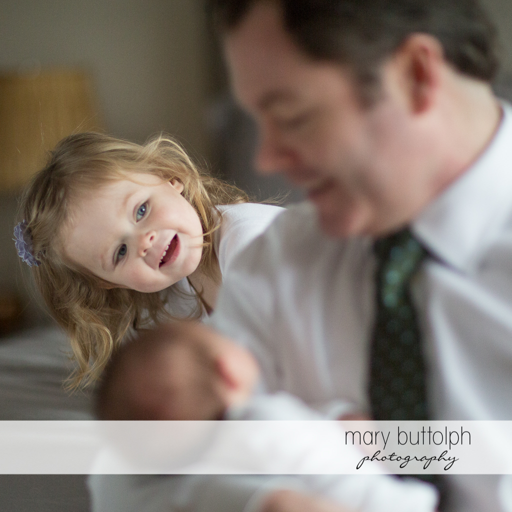 Girl watches her father carrying her new baby brother at Skaneateles Newborn Photography