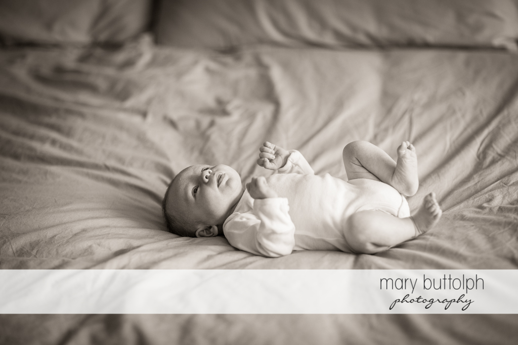 Baby looks at the ceiling while lying in bed at Skaneateles Newborn Photography