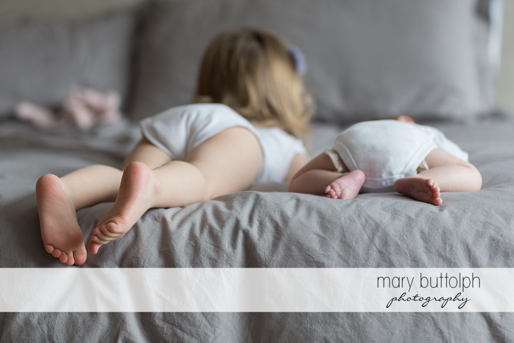 Girl and her baby brother lie together in bed at Skaneateles Newborn Photography