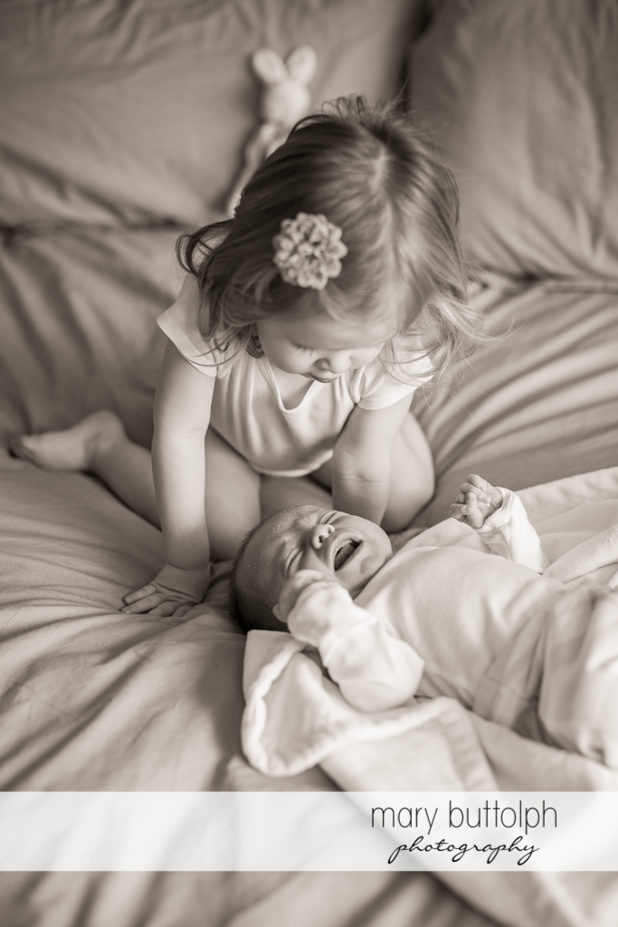 Girl doesn't know how to stop baby from crying in bed at Skaneateles Newborn Photography