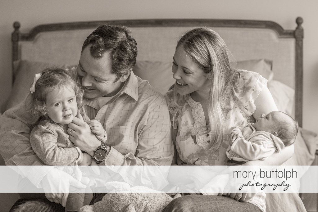 The family of four pose together in bed at Skaneateles Newborn Photography