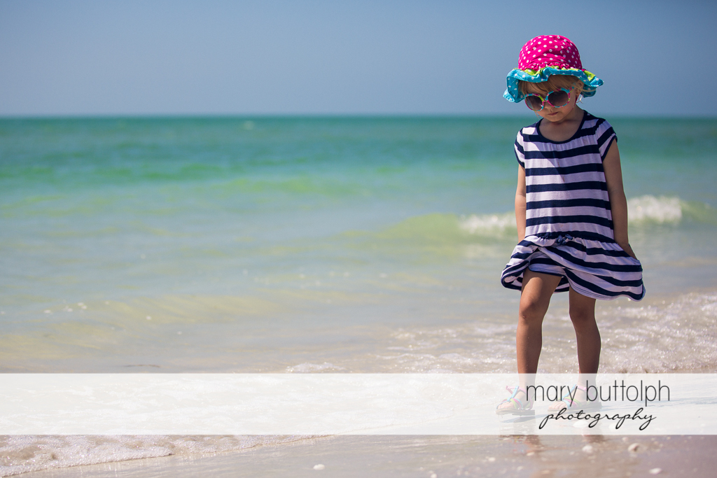 Girl with hat and sunglasses walks along the shore at Sanibel Island Vacation