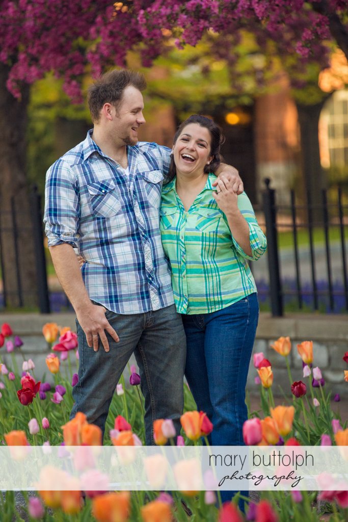Couple stroll in the garden full of flowers at Skaneateles Engagement