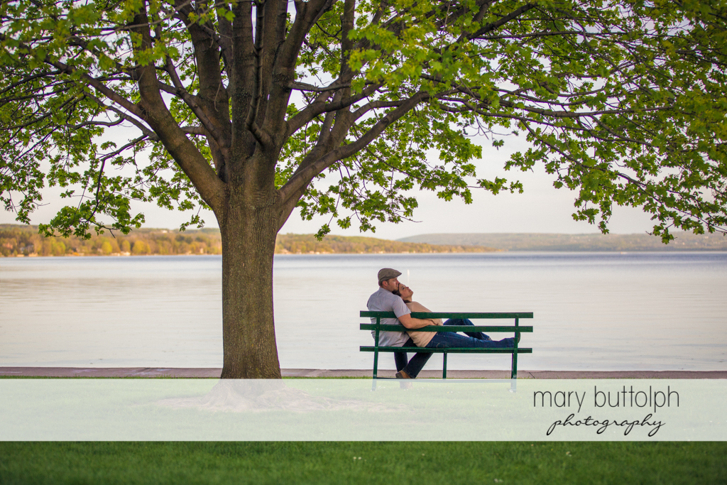 Couple relax on a bench in front of the lake at Skaneateles Engagement