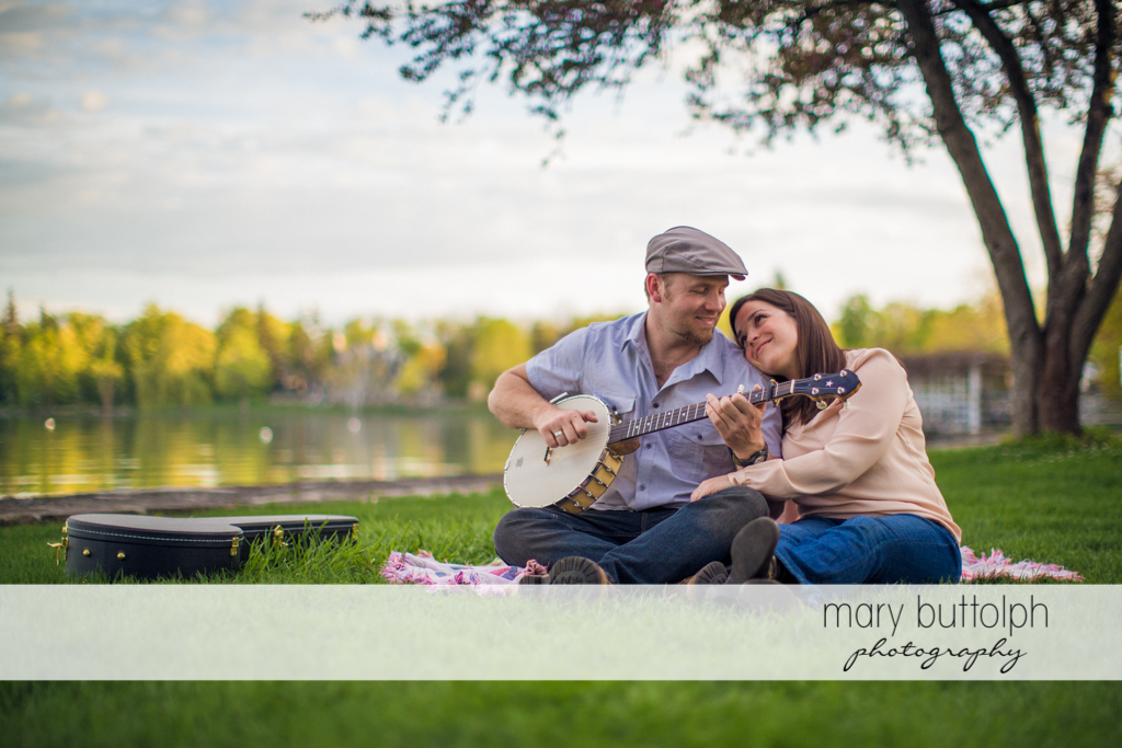Man plays the banjo for his female companion near the lake at Skaneateles Engagement