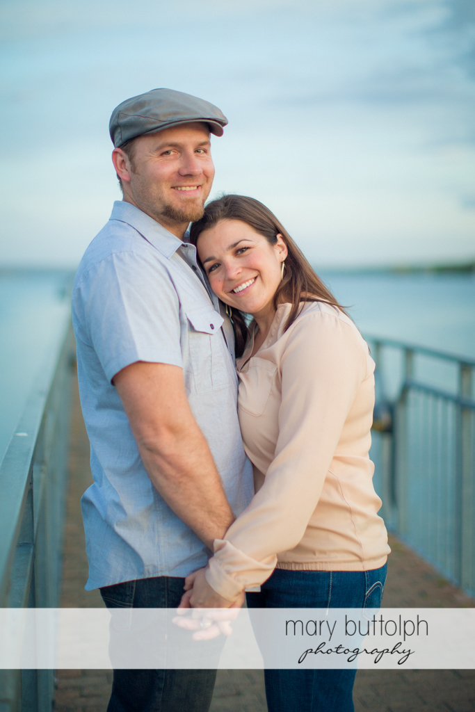 Couple hold hands near the lake at Skaneateles Engagement