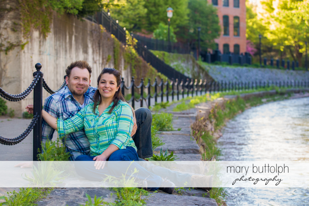 Couple sit near a fence by the lake at Skaneateles Engagement