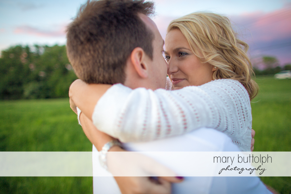 Couple rub noses in the field at Skaneateles Engagement