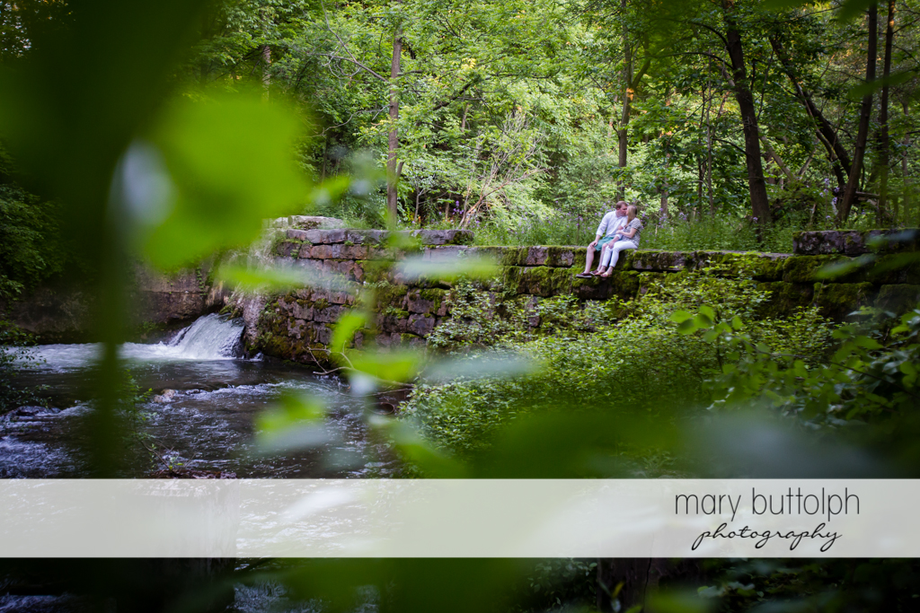 Couple sit by the lake at Skaneateles Engagement