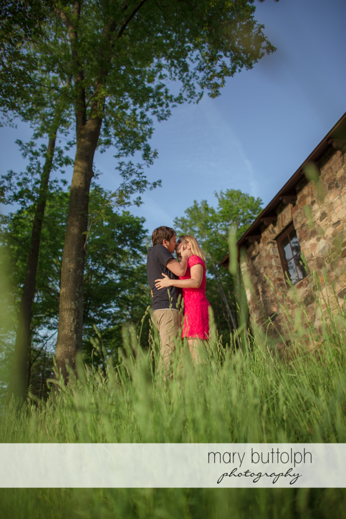 Couple kiss near an old house at Green Lakes State Park Engagement