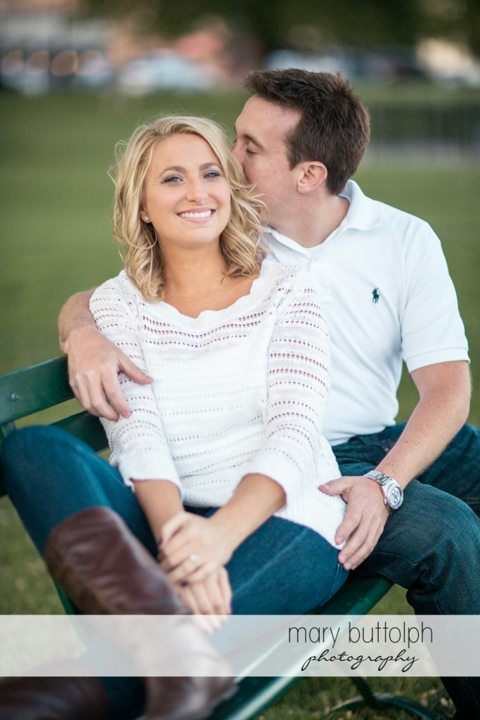 Couple sit on a bench in the garden at Skaneateles Engagement