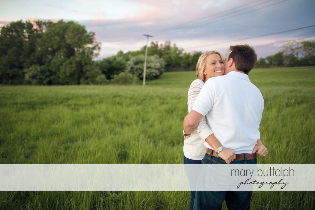 Couple embrace in the field at Skaneateles Engagement