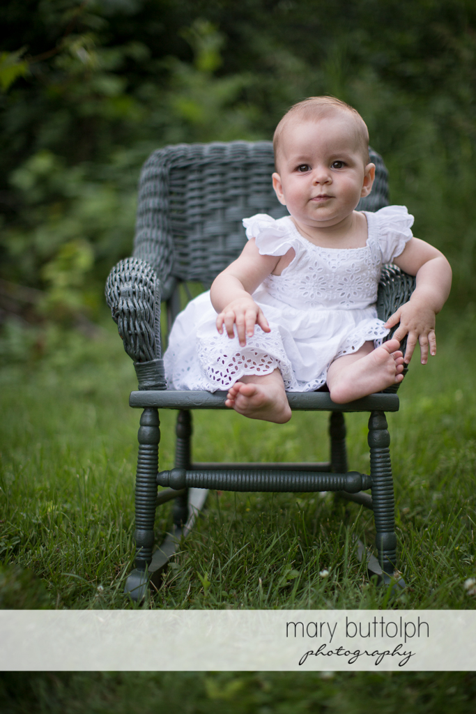 Baby sits on a chair in the backyard at Skaneateles Family