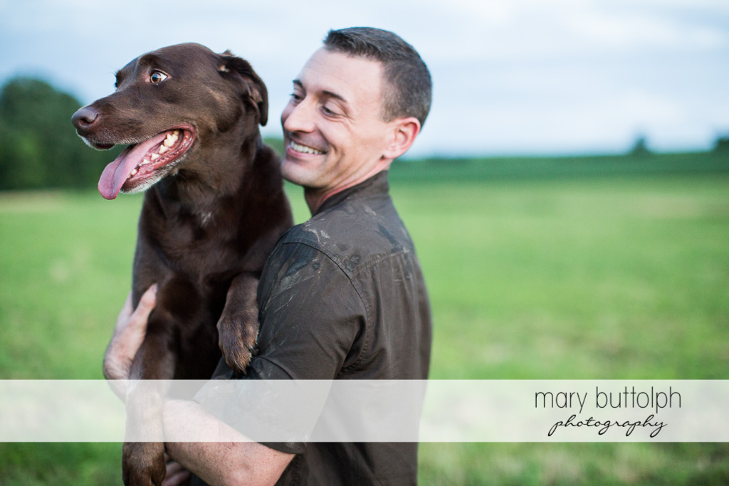 Man poses with his pet dog in the field at Lockwood Lavender Farm Engagement