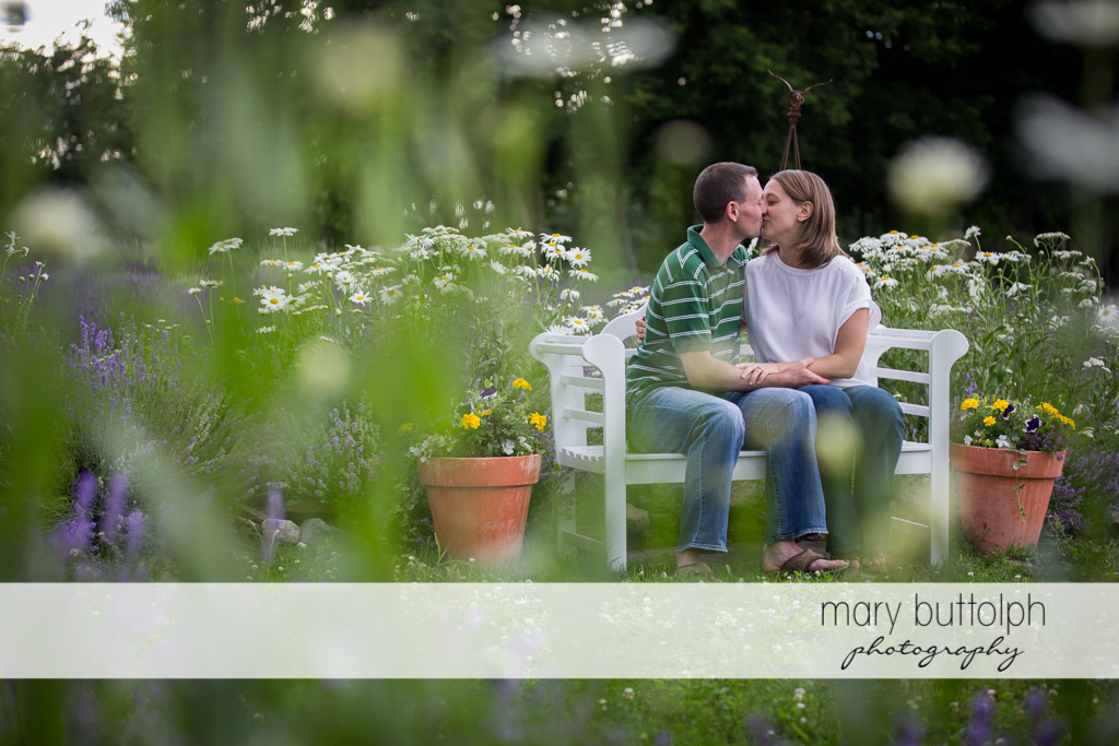 Couple kiss in the garden full of flowers at Lockwood Lavender Farm Engagement