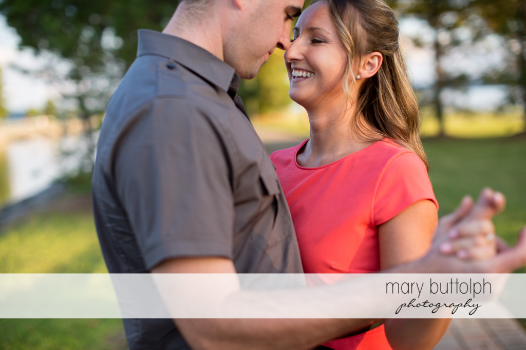 Couple in a tender moment near the river at Emerson Park Engagement