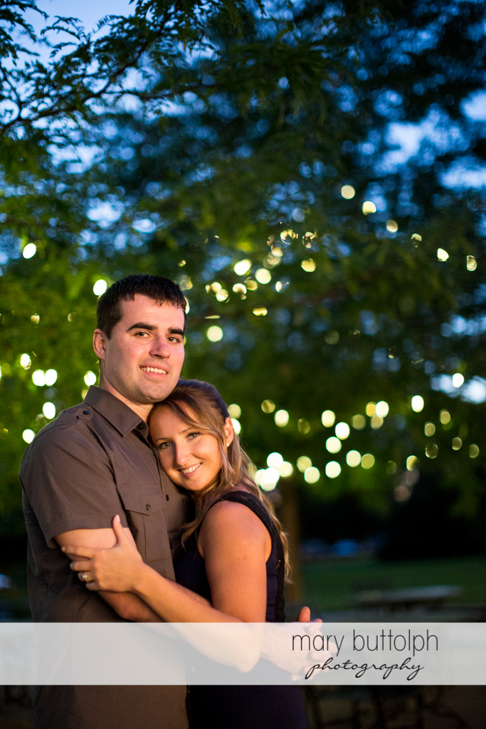 Couple stand under the tree lights at Emerson Park Engagement