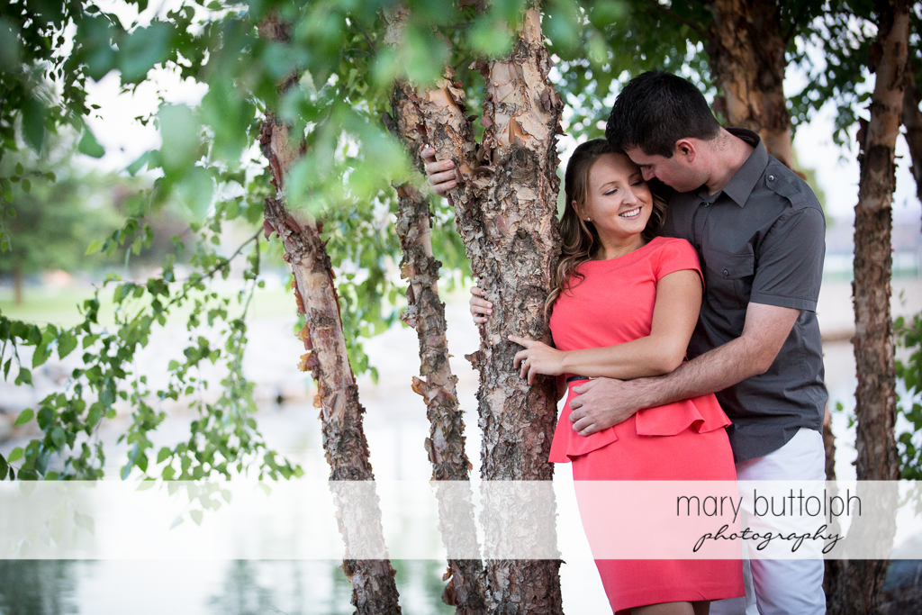 Couple show their romantic side near trees by the river at Emerson Park Engagement